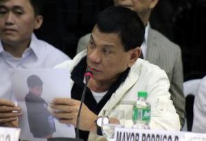Davao Mayor Rodrigo Duterte showing photo of David Bangayan, a.k.a. David Tan, during Senate probe on rice smuggling.